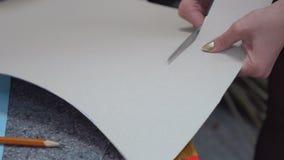 Το ψαλίδι κόβει το έγγραφο Πεπιεσμένο χαρτί Κοπή σε ένα χαρτόνι απόθεμα βίντεο