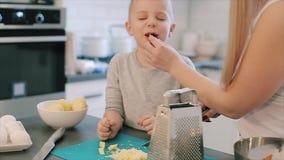 Το τέμνον τυρί μητέρων και δίνει στο γιο της στην κουζίνα Νέα μητέρα και χαριτωμένος όμορφος γιος με το μεγάλο μαγείρεμα ματιών φιλμ μικρού μήκους