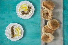 """Το τυρί γάλακτος της ανατολικής μαλακής αίγας Labneh labanehmiddle με το ελαιόλαδο, za """"atar, λεμόνι, ψωμί pita, εξυπηρέτησε στην στοκ φωτογραφία με δικαίωμα ελεύθερης χρήσης"""