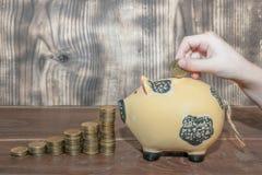 Το χέρι βάζει ένα νόμισμα σε μια piggy τράπεζα στοκ φωτογραφίες