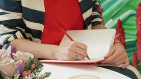 Το χέρι μιας νέας γυναίκας σε ένα ριγωτό κοστούμι παίρνει τις σημειώσεις με ένα μολύβι σε ένα κόκκινο σημειωματάριο φιλμ μικρού μήκους