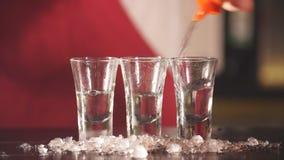 Το χέρι μπάρμαν χύνει τη βότκα στα κοντά διαφανή ποτήρια με τα τσιπ πάγου για την ψύξη φιλμ μικρού μήκους