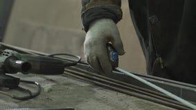 Το χέρι του σιδηρουργού μετρά το απαραίτητο μήκος των ράβδων σιδήρου απόθεμα βίντεο