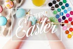 Το χέρι παιδιών χρωμάτισε τα βρασμένες αυγά Πάσχας, τα χρώματα και τις βούρτσες σε έναν άσπρο πίνακα Προετοιμασία για τις διακοπέ στοκ φωτογραφία με δικαίωμα ελεύθερης χρήσης