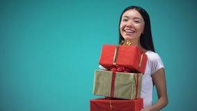 Το χαμογελώντας κορίτσι που κρατά πολλά giftboxes, φεστιβάλ παρουσιάζει, στεμένος στο μπλε υπόβαθρο φιλμ μικρού μήκους