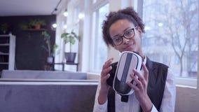 Το χαμογελώντας μελαχροινό ξεφλουδισμένο κορίτσι εφήβων στα γυαλιά βάζει στη μάσκα εικονικής πραγματικότητας στη κάμερα απόθεμα βίντεο