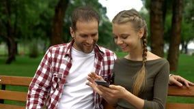 Το χαριτωμένο έφηβη κόρη που παρουσιάζει αστείο βίντεο στο κινητό τηλέφωνο στον πατέρα, χαλαρώνει στο πάρκο στοκ εικόνες
