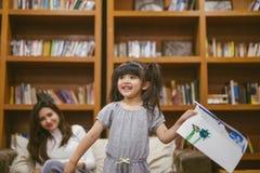 Το χαριτωμένο μικρό κορίτσι που χρωματίζει μια εικόνα με τη μητέρα και παρουσιάζει εργασία της στο σπίτι στοκ εικόνα με δικαίωμα ελεύθερης χρήσης