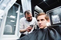 Το χαριτωμένο μικρό παιδί παίρνει το κούρεμα από τον κομμωτή στο barbershop στοκ εικόνα