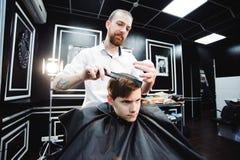 Το χαριτωμένο μικρό παιδί παίρνει το κούρεμα από τον κομμωτή στο barbershop στοκ φωτογραφία