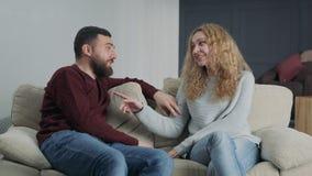 Το χαριτωμένο νέο ζεύγος κάθεται σε έναν καναπέ στο σπίτι απόθεμα βίντεο