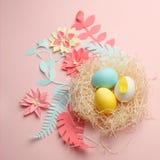 Το χρώμα Πάσχα εγγράφου Origami ανθίζει, αυγά στη φωλιά στο υπόβαθρο χρώματος, ευχετήρια κάρτα εστέρα, λουλούδι εγγράφου origami στοκ φωτογραφίες με δικαίωμα ελεύθερης χρήσης