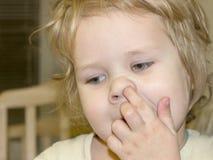 Το παιδί επιλέγει τη μύτη του και προσπαθεί να πάρει το στεγνωμένο salpi από τους κόλπους στοκ φωτογραφίες με δικαίωμα ελεύθερης χρήσης