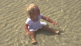 Το παιδί κάθεται στη θάλασσα Συνεδρίαση μικρών κοριτσιών στο νερό στην παραλία απόθεμα βίντεο