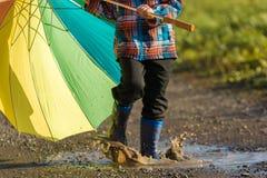 Το παιδί παίζει με τη ζωηρόχρωμη ομπρέλα σε μια λακκούβα στοκ φωτογραφία