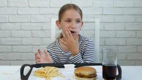 Το παιδί που τρώει το γρήγορο φαγητό, παιδί τρώει το χάμπουργκερ στο εστιατόριο, χυμός κατανάλωσης κοριτσιών απόθεμα βίντεο