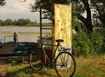 Το παλαιό ποδήλατο στέκεται κοντά στον παλαιό τηλεφωνικό θάλαμο στοκ φωτογραφία