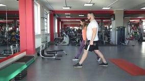 Το παχύ καυκάσιο άτομο με μια γενειάδα στη γυμναστική εκτελεί μια άσκηση κάθεται οκλαδόν με τους αλτήρες κάτω από τη επίβλεψη του απόθεμα βίντεο