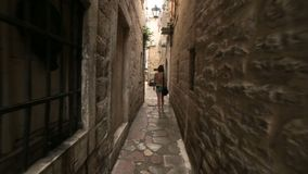 Το περπάτημα κοριτσιών τουριστών κατά μήκος του στενού η οδός της παλαιάς μεσογειακής κωμόπολης ή της πόλης στο Μαυροβούνιο όπως  απόθεμα βίντεο
