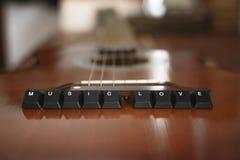 Το πληκτρολόγιο κουμπώνει τη μουσική εγγραφής αγαπά πάνω από την ακουστική κιθάρα Ξύλινη ανασκόπηση στοκ φωτογραφία