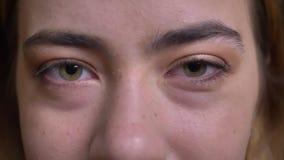 Το πορτρέτο κινηματογραφήσεων σε πρώτο πλάνο του νέου όμορφου καυκάσιου θηλυκού προσώπου με τα πράσινα μάτια που κοιτάζουν επίμον απόθεμα βίντεο