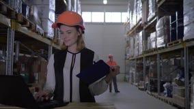 Το πορτρέτο της γυναίκας υπαλλήλων στο σκληρό καπέλο λειτουργεί με το lap-top και κάνει τις σημειώσεις στο σημειωματάριο στο υπόβ φιλμ μικρού μήκους