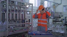 Το πορτρέτο του αρσενικού τεχνικών εργοστασίων στις φόρμες βάζει το κράνος και δόσιμο των αντίχειρων επάνω με τα εργαλεία για τις απόθεμα βίντεο