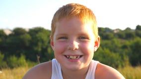 Το πορτρέτο του ευτυχούς κόκκινου αγοριού τρίχας με τις φακίδες γελά υπαίθριος Λατρευτό όμορφο μωρό που εξετάζει τη κάμερα με χαρ απόθεμα βίντεο