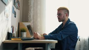 Το πορτρέτο του όμορφου νεαρού άνδρα στα γυαλιά με την κίτρινη τρίχα παρουσιάζει αντίχειρα στη κάμερα Σπίτι Freelancer που λειτου απόθεμα βίντεο
