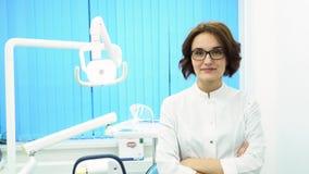 Το πορτρέτο των όμορφων νέων μόνιμων όπλων οδοντιάτρων γυναικών διέσχισε στο οδοντικό γραφείο κλινικών Βέβαιος γιατρός μέσα απόθεμα βίντεο