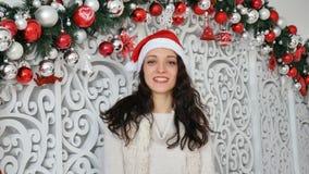 Το πορτρέτο χαμογελώντας της αρκετά νέας γυναίκας στο κόκκινο καπέλο santa που εξετάζει τη κάμερα στα Χριστούγεννα διακόσμησε το  φιλμ μικρού μήκους