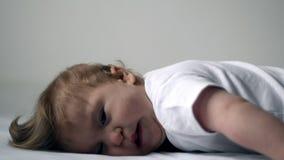 Το πρόσωπο με ειδικές ανάγκες παιδιών ενός έτους βρεφών κάτω από το κρεβάτι προσπαθεί να ανυψώσει το κεφάλι του φιλμ μικρού μήκους