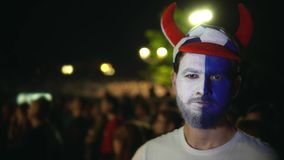 Το πρόσωπο με το χρώμα στο πρόσωπο είναιη χάνοντας ομάδα ποδοσφαίρου, εξετάζει τη κάμερα 4K απόθεμα βίντεο