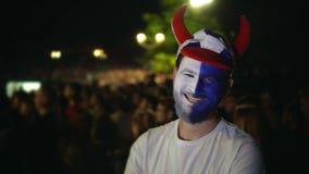 Το πρόσωπο χρωμάτων προσώπων κάνει τη ομάδα ποδοσφαίρου ευτυχησμένη, εξετάζει το πλήθος υποβάθρου καμερών φιλμ μικρού μήκους