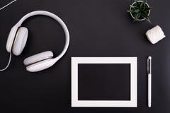 Το πρότυπο, το πλαίσιο φωτογραφιών, τα ακουστικά, η μάνδρα, και ο κάκτος γράφουν το αντικείμενο στο μαύρο υπόβαθρο στοκ φωτογραφία με δικαίωμα ελεύθερης χρήσης