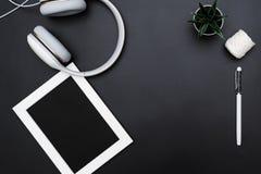 Το πρότυπο, το πλαίσιο φωτογραφιών, τα ακουστικά, η μάνδρα, και ο κάκτος γράφουν το αντικείμενο στο μαύρο υπόβαθρο στοκ φωτογραφία