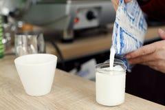 Το Barista στον ξύλινο πίνακα φραγμών στον καφέ χύνει το γάλα στο ποτήρι για να προετοιμαστεί latte στοκ εικόνες