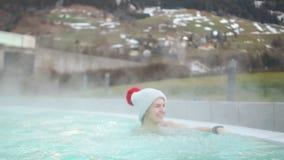 Το Brunette με ένα δρεπάνι σε ένα πλεκτά καπέλο και ένα μαγιό βουτά σε μια καυτή λίμνη το χειμώνα ενάντια στο σκηνικό του χιονιού απόθεμα βίντεο