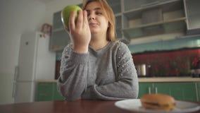 Το Chubby κορίτσι σκέφτεται ότι πρέπει να φάει ένα νόστιμο χάμπουργκερ ή ένα juicy πράσινο μήλο Δύσκολη επιλογή μεταξύ υγιούς και φιλμ μικρού μήκους