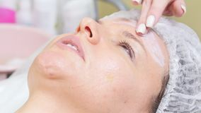 Το Cosmetologist αρχίζει την κρέμα στο μέτωπο του πελάτη που κάνει τον καλλυντικό καθαρισμό διαδικασιών του προσώπου μέσα απόθεμα βίντεο