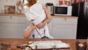 Το Mom βάζει το καπέλο του αρχιμάγειρα στο χαριτωμένο μωρό της, αλλά το παιδί το παίρνει μακριά απόθεμα βίντεο