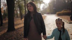 Το Mom και η κόρη περπατούν κατά μήκος μιας λεωφόρου που σκορπίζεται με το κίτρινο φύλλωμα φθινοπώρου Ευτυχής οικογένεια σε έναν  φιλμ μικρού μήκους