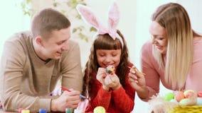 Το Mom και ο μπαμπάς που κρατούν μια βούρτσα, που προσέχει ως κόρη χρωματίζουν το αυγό Πάσχας απόθεμα βίντεο