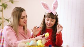 Το Mom κρατά το αυγό Πάσχας, και η κόρη μου το διακοσμεί με τα δάχτυλά σας φιλμ μικρού μήκους