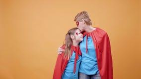 Το Mom φιλά την κόρη της στο μέτωπο ενώ ντύνεται ως superheroes απόθεμα βίντεο