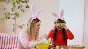 Το Mom προετοιμάζεται για Πάσχα, και η κόρη της καλύπτει τα μάτια της με τα χρωματισμένα αυγά απόθεμα βίντεο