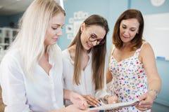 Τρία έξυπνος-που κοιτάζουν όμορφες γυναίκες που φορούν τα άσπρα πουκάμισα εξετάζουν το ράβοντας περιοδικό Μόδα, εργαστήριο του ρά στοκ εικόνα