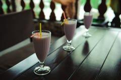 Τρία βάζα του ρόδινου μούρου milkshakes με τα άχυρα στον παλαιό ξύλινο πίνακα στοκ φωτογραφίες