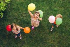 Τρία ευτυχή παιδάκια που παίζουν με τα ζωηρόχρωμα μπαλόνια στοκ εικόνα με δικαίωμα ελεύθερης χρήσης