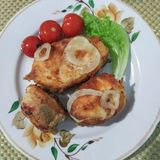 Τρία κομμάτια των τηγανισμένων ψαριών με τα δαχτυλίδια κρεμμυδιών σε ένα πιάτο στοκ φωτογραφία με δικαίωμα ελεύθερης χρήσης